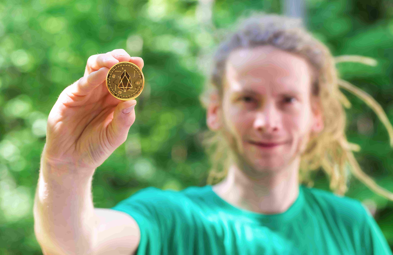 pessoa segurando uma moeda da eos criptomoeda
