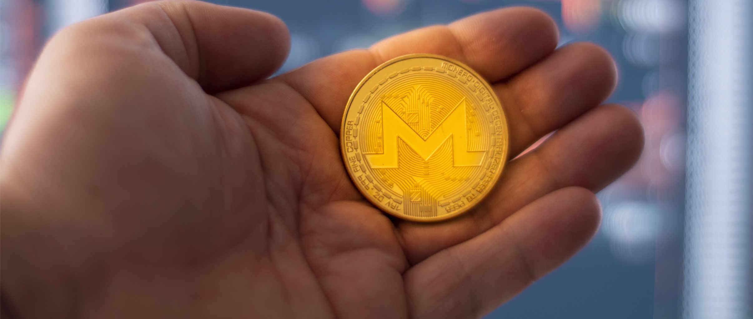 moeda monero na mão
