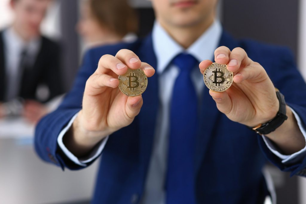 homem segurando duas moedas de bitcoin