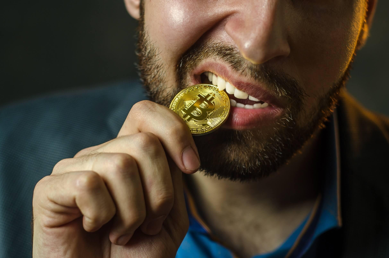 homem mordendo moeda física de bitcoin