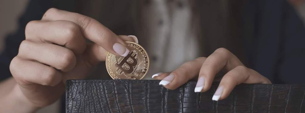 mulher colocando bitcoin dentro da carteira