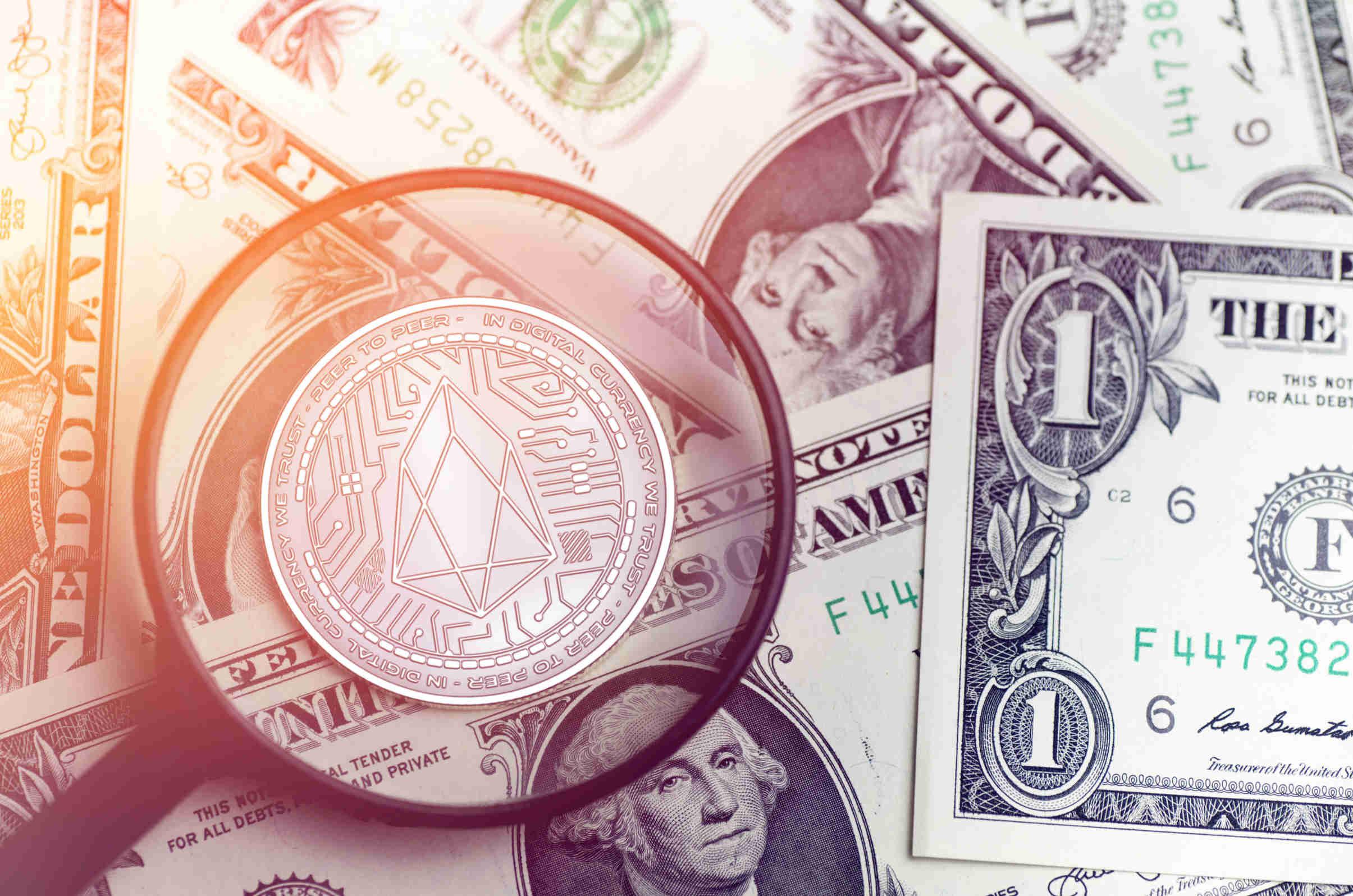 moeda eos em uma lupa no fundo moedas em dólar