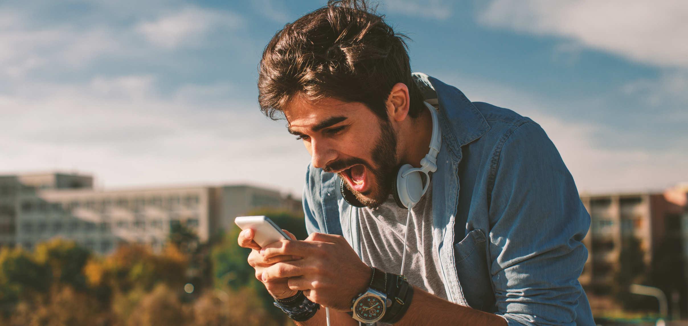 homem vendo celular portfólio de criptomoedas