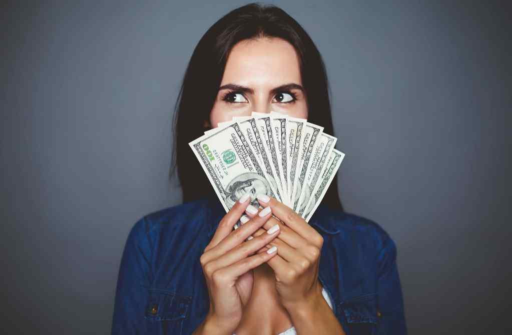 Lastro - mulher segurando notas de dólar