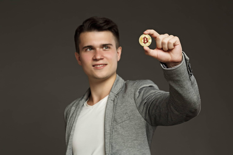 como investir em bitcoin? - homem segurando moeda física de bitcoin