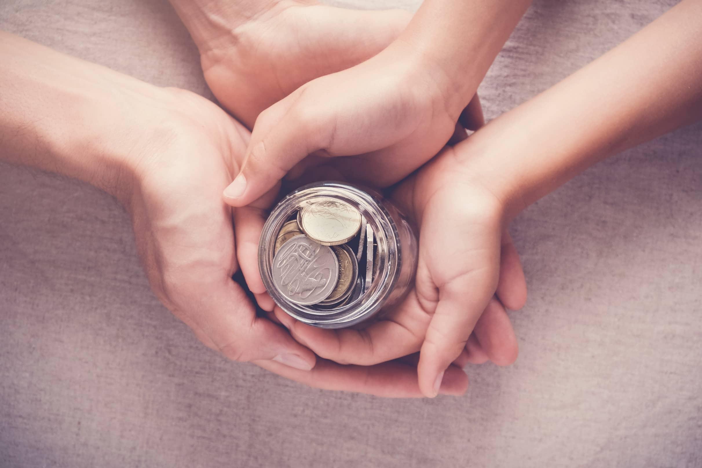 Renda fixa - mãos segurando um pote de moedas
