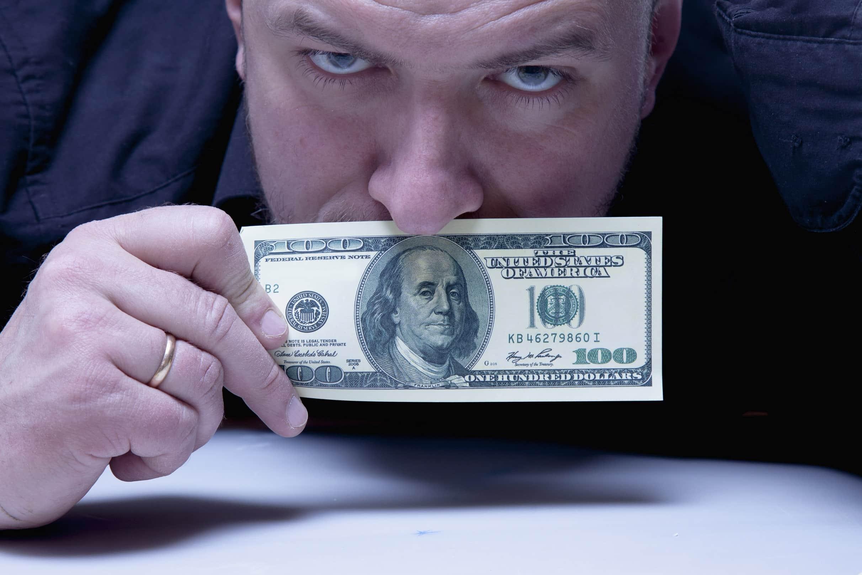 visão de mercado: homem segurando cédula de dólar