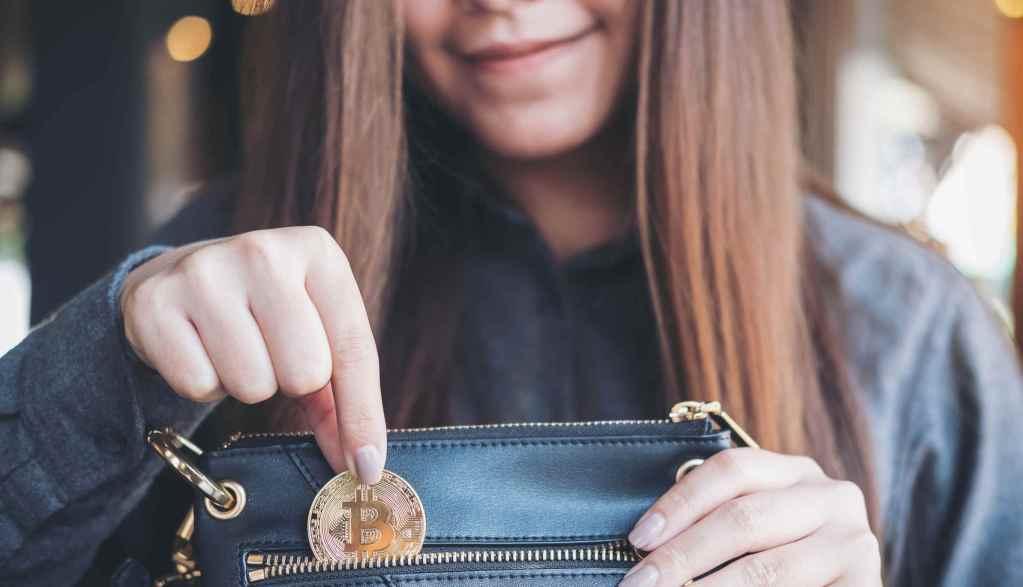 Carteiras de bitcoin online, mulher guaradando moeda de bitcoin na carteira