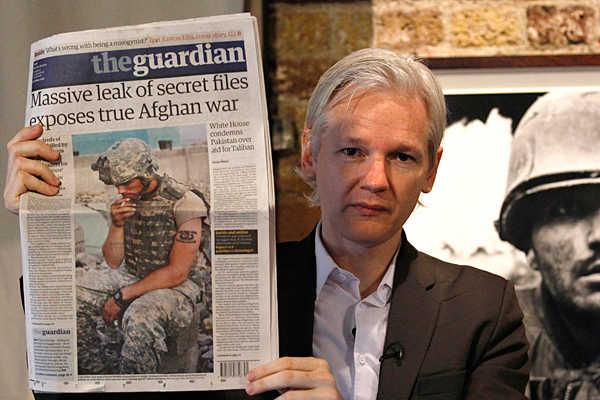 Julian Assange do Wikileaks segurando jornal
