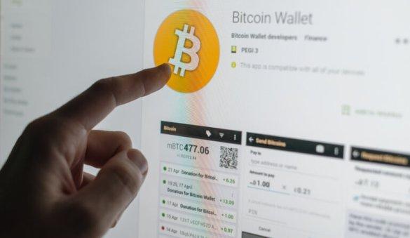 Dedo apontando para recorde de carteira de Bitcoin