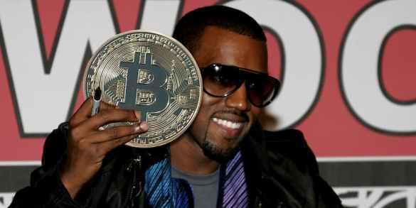 Kanye West segurando uma moeda de bitcoin