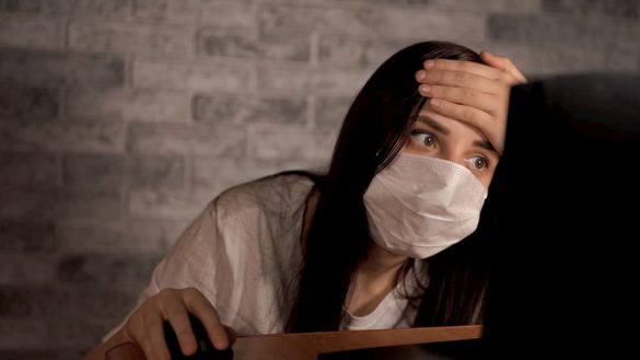 Mulher de máscara na frente do computador