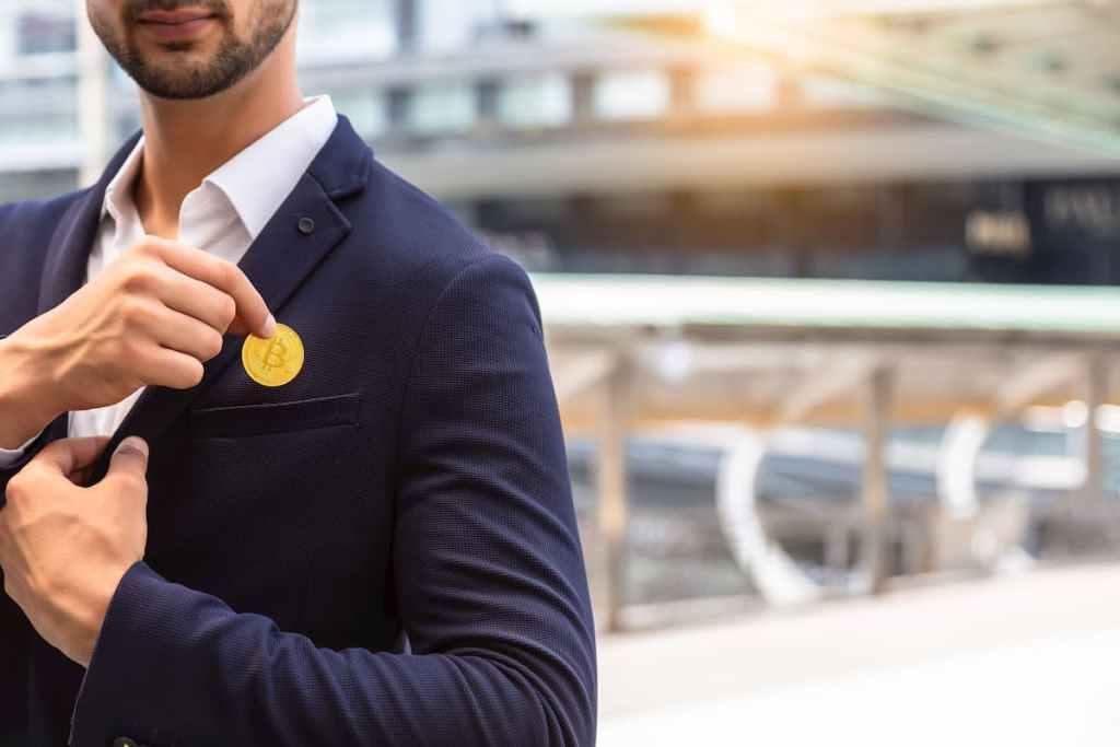 Homem de terno segurando Bitcoin