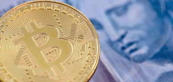 Moeda de bitcoin e nota de real lado a lado