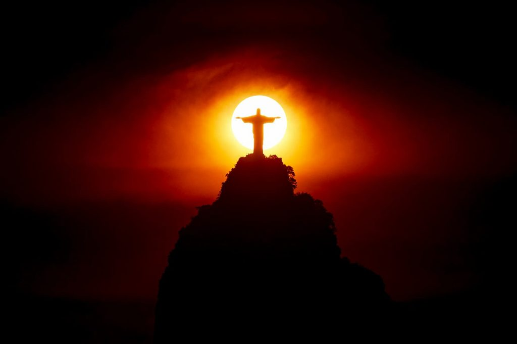Cristo rendetor atrás sol no escuro