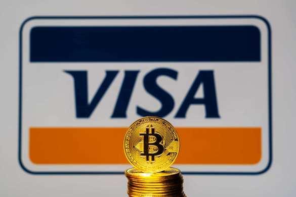 Moeda de Bitcoin e logo antigo da Visa atrás