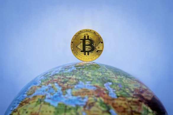 moeda de bitcoin em cima do globo terrestre