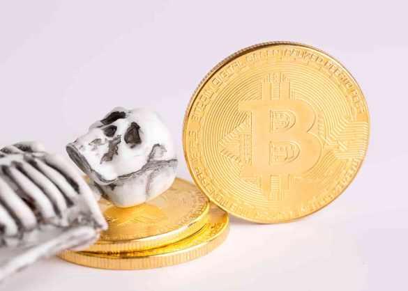 esqueleto deitado em moeda de bitcoin