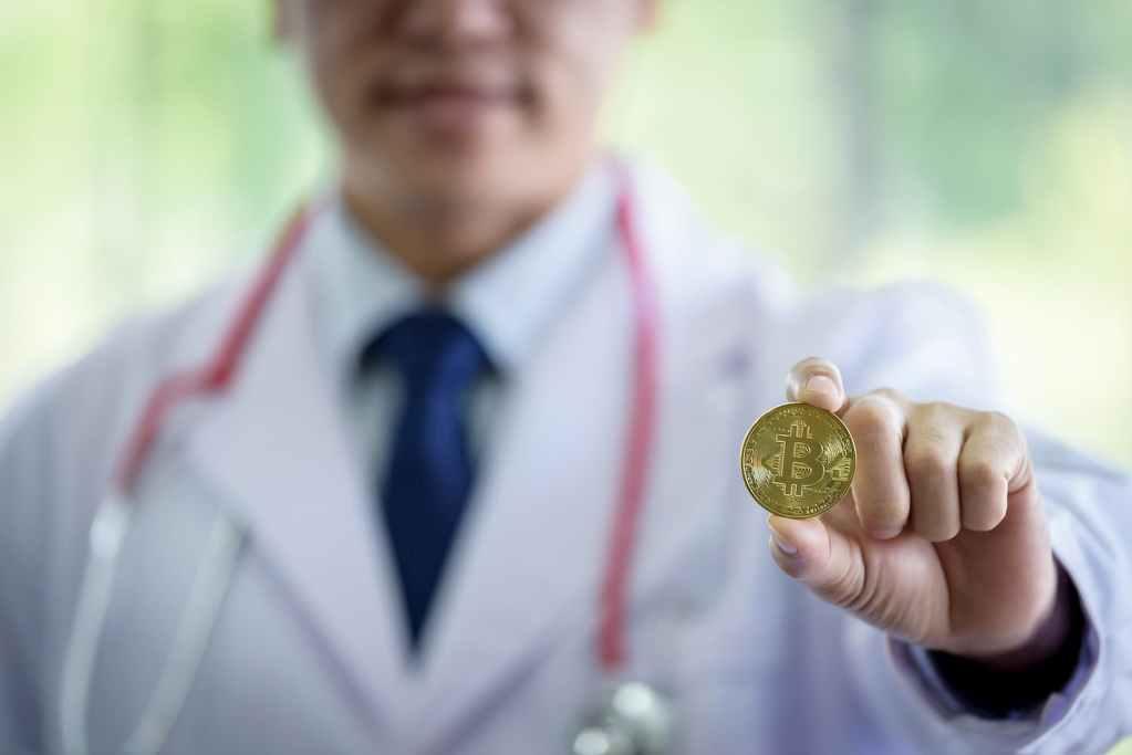 médico segurando bitcoin