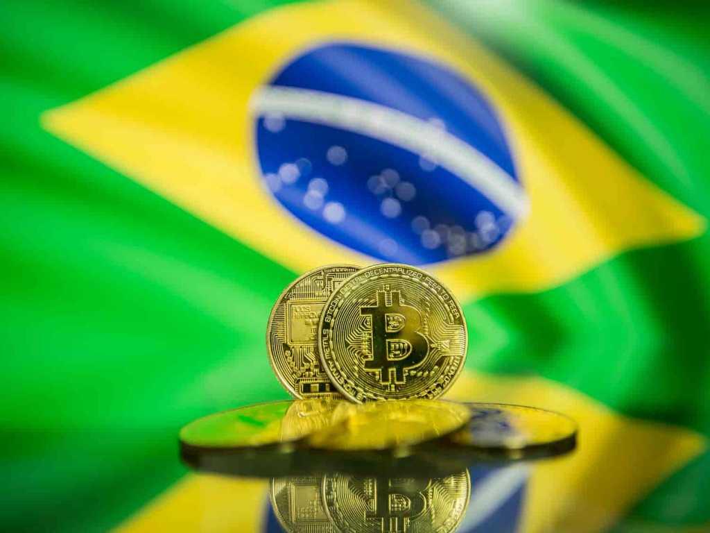 Moeda de Bitcoin com bandeira do Brasil ao fundo