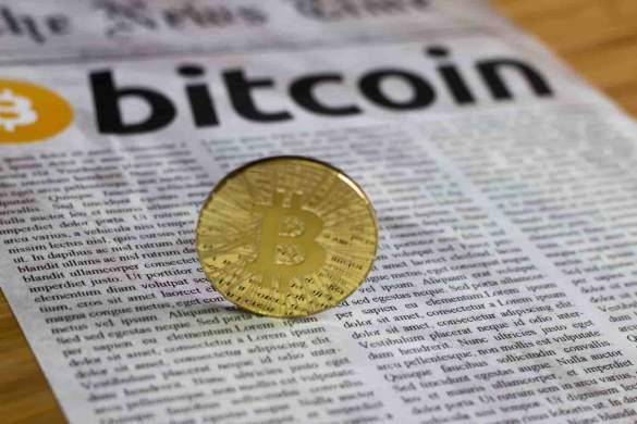 jornal ao fundo com moeda de bitcoin dourada de pé