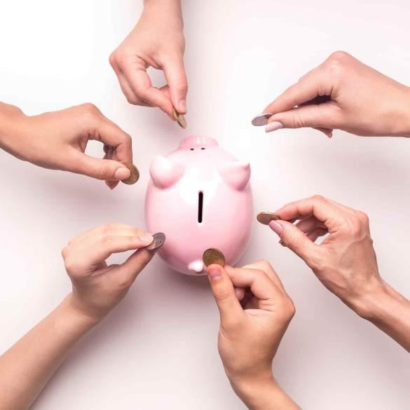 Mãos colocando dinheiro em porquinho