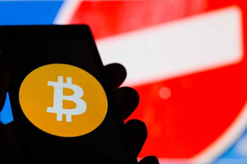Smartphone com logo do bitcoin e sinal de censura ao fundo