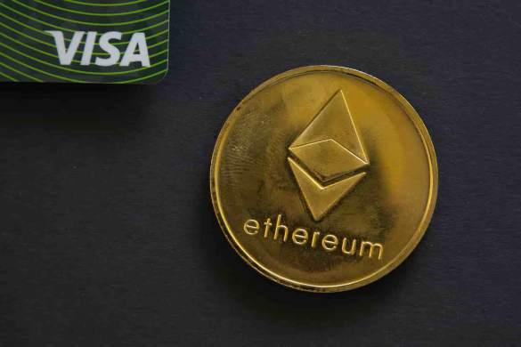 Cartão visa ao lado de moeda do ethereum