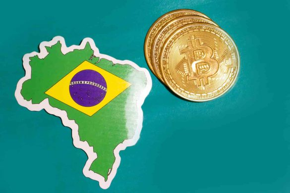 Moeda de bitcoin ao lado do território brasileiro