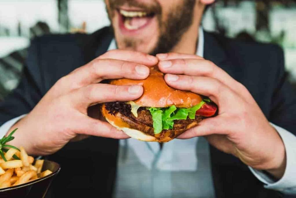 homem comendo sanduíche contaminado