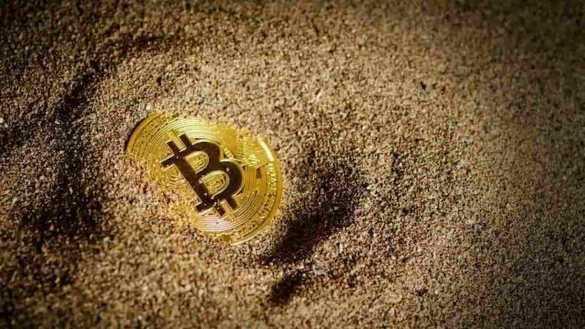 Moeda de bitcoin enterrada na areia